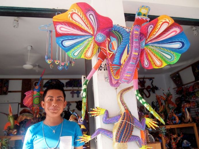 La Crucecita is a small community, located (walkably) near the Santa Cruz Bay, about five kilometres from the Camino Real Zaashila. This young man was very proud of the bright sculptures in the shop. Credit: Therese Kehler, December 2016