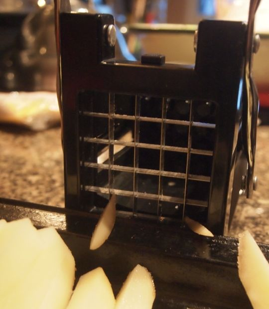 The potato is forced through the sharp blades of the Starfrit Fry Cutter, creating perfectly cut fries.