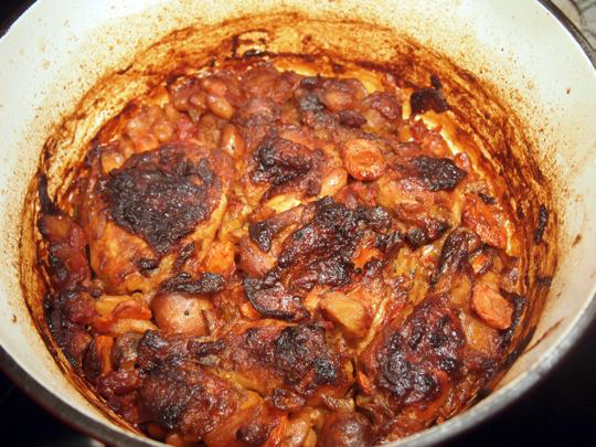 After baking in the oven, the cassoulet will start to develop a thick, dark crust.