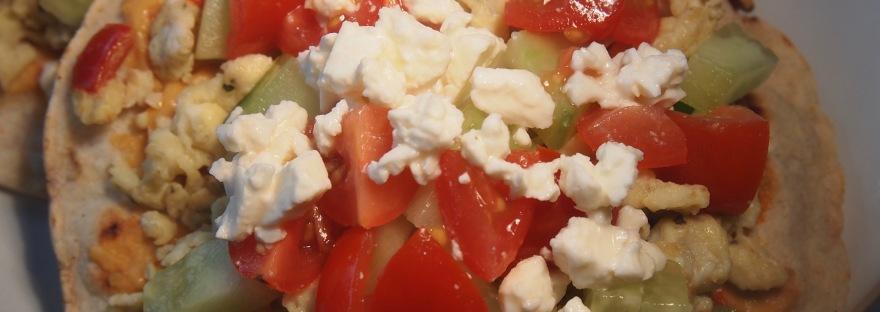 A Mediterranean Breakfast Tostada, with scrambled eggs, hummus, tomatoes, cucumber and feta.