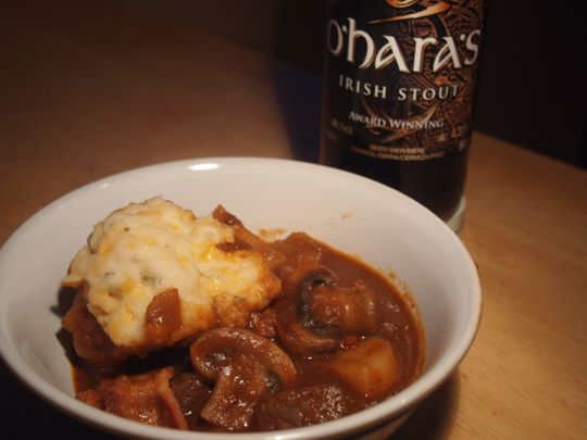 A bowl of dumpling-topped Guinness Beef Stew served, appropriately, with an Irish stout beer.