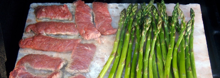 Thin-slice steak and asparagus cooking on salt block on top of the barbecue.