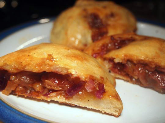 A filling of sausages, cabbage, onion and barbecue sauce neatly baked inside a bun.