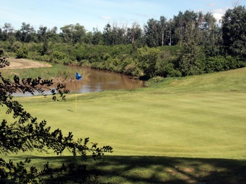 Looking back at the fifth green of Barrhead Golf Course, with the Paddle River flowing behind it.