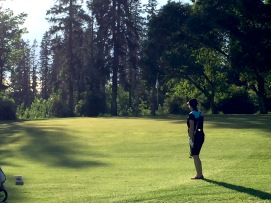 Sun slants through the trees onto a green during an evening round at J.R. Golf Course.