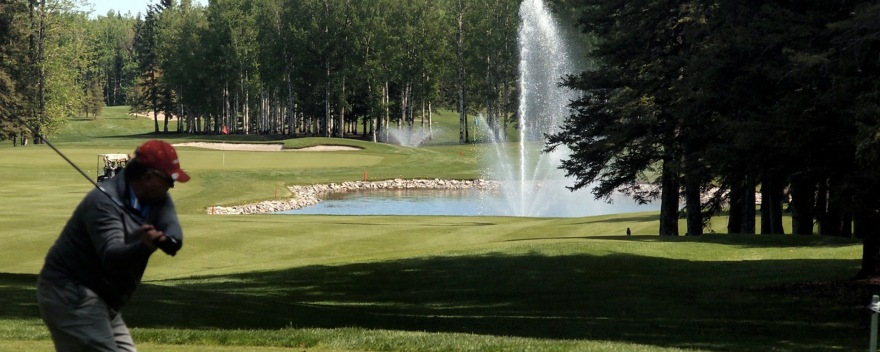 The first hole at Sundre Golf Club — trees to the left, water to the right.