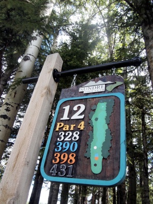 A tee-box sign nestles in the trees at Sundre Golf Club.
