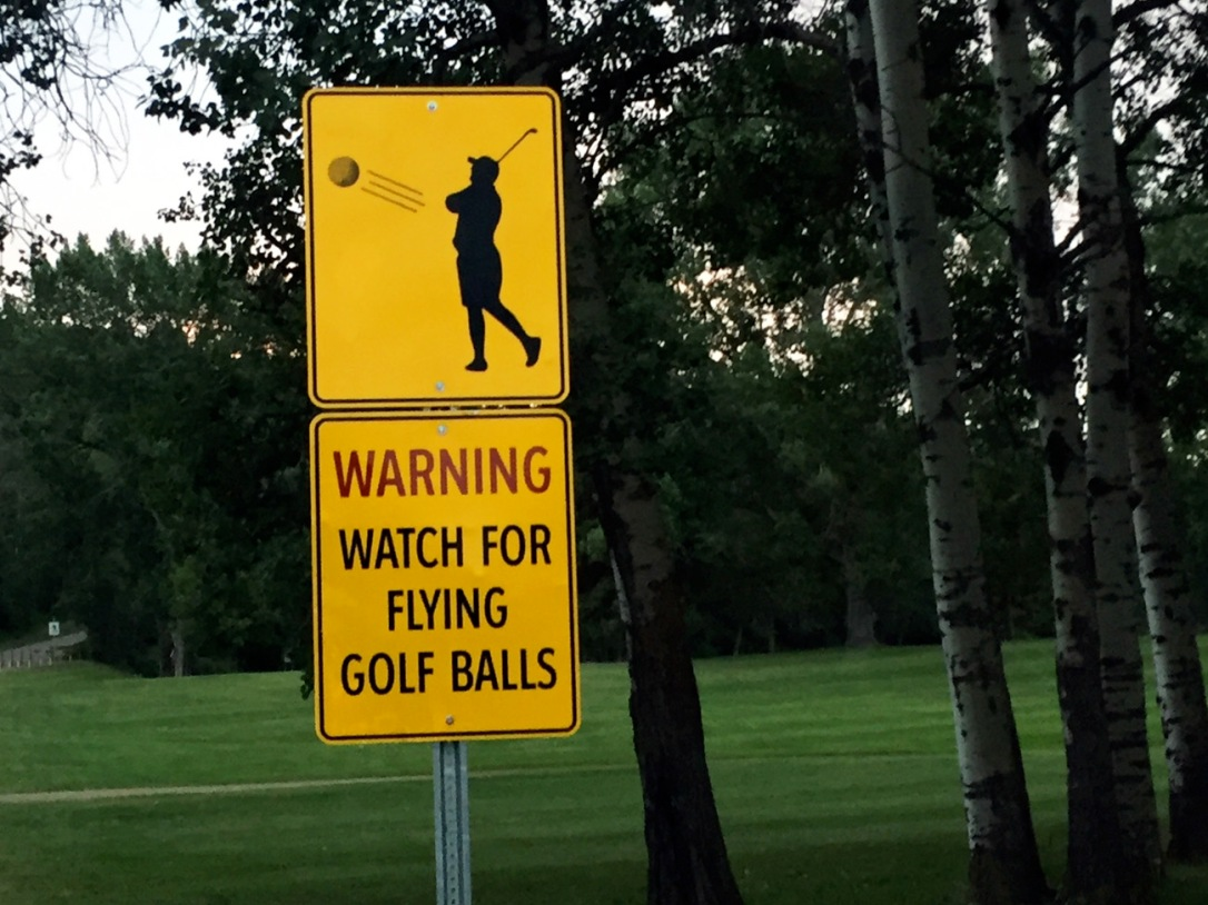 These signs at the Devon Golf Course aren't kidding. Golfers are hitting across the road on back-to-back fairways.